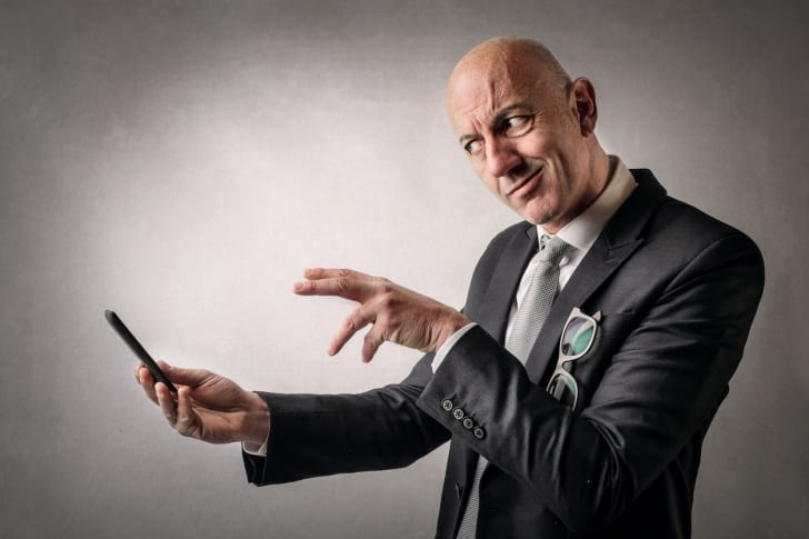 A person in a suit working magic on a cell phone