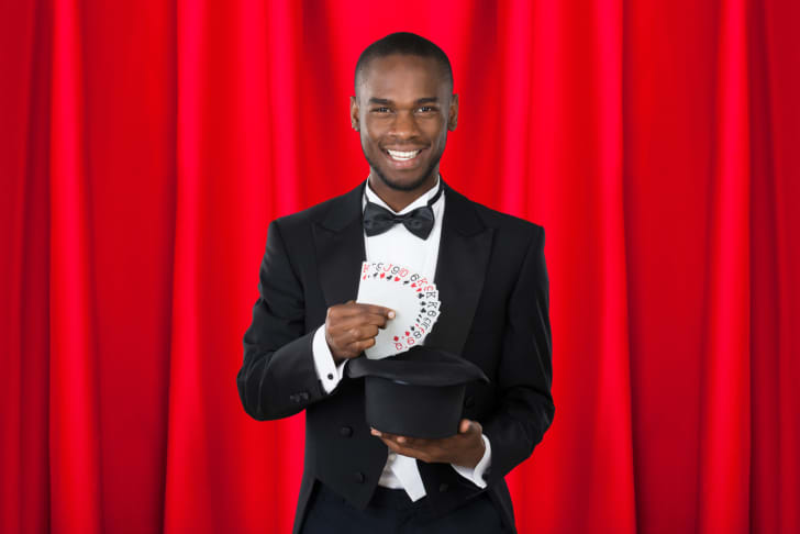 A happy magician showing a trick with playing cards
