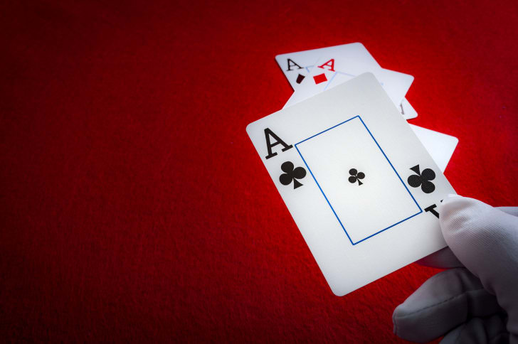 A white-gloved magician holding playing cards on a red background