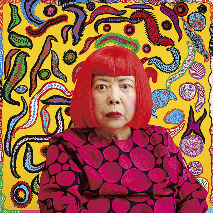 A portrait of Yayoi Kusama wearing a red wig