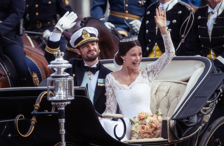 Prince Carl Philip of Sweden and his wife Princess Sofia ride in a carriage on their wedding day.