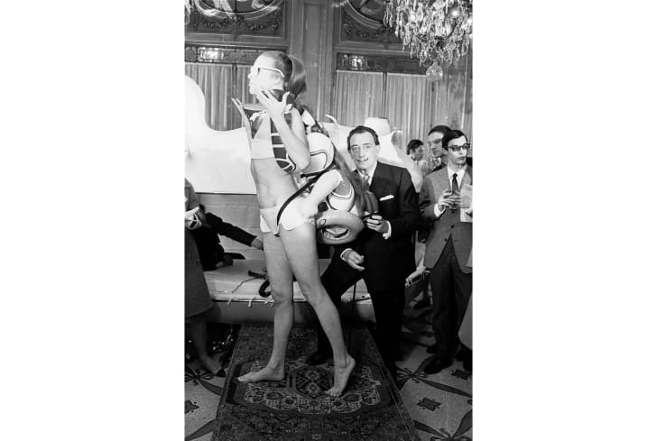 Dalí poses next to a model wearing one of his bathing suits.