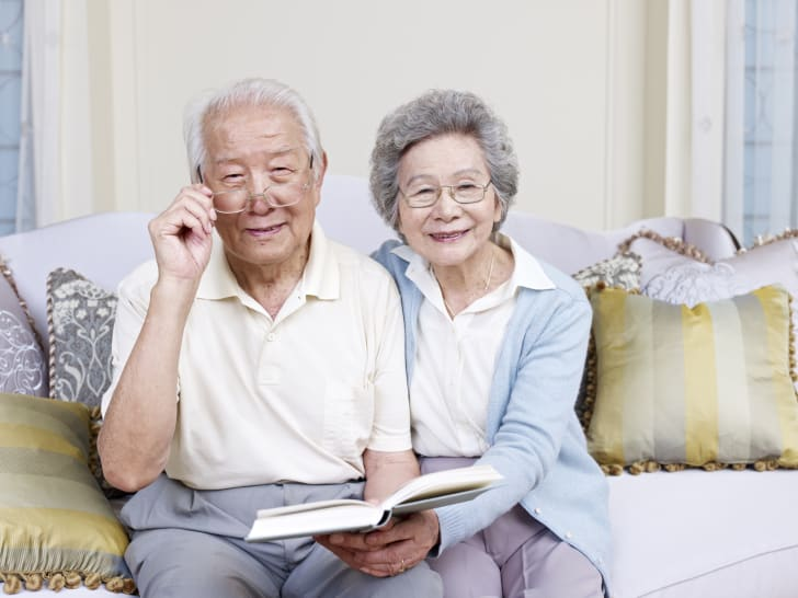 elderly couple reads book together