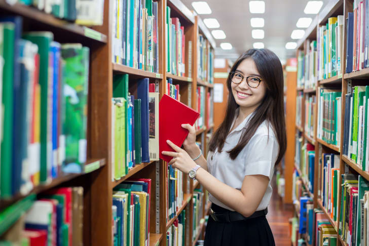 young woman takes book from library bookshelf