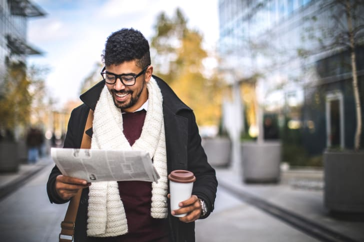 happy man reads newspaper as he walks