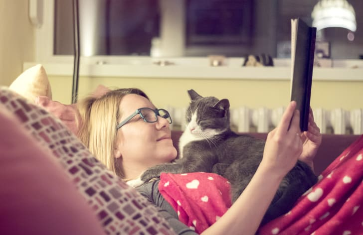 woman reads book while cat lays on her chest