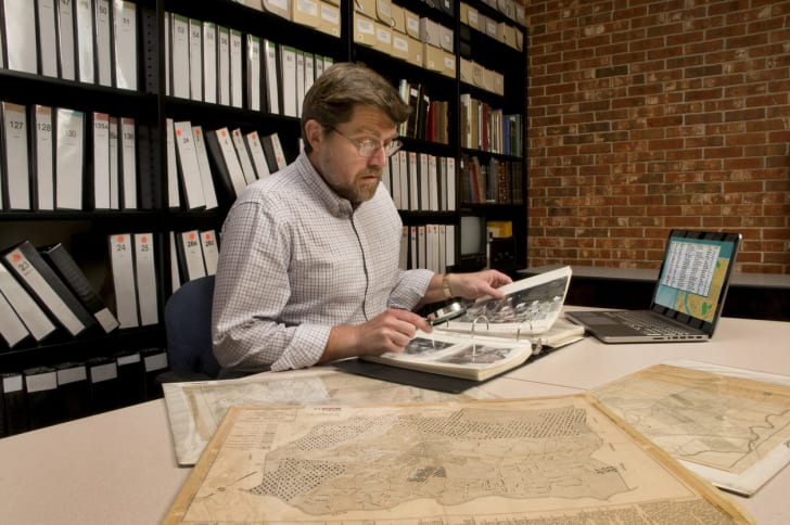 Genealogists in archive examining archival materials