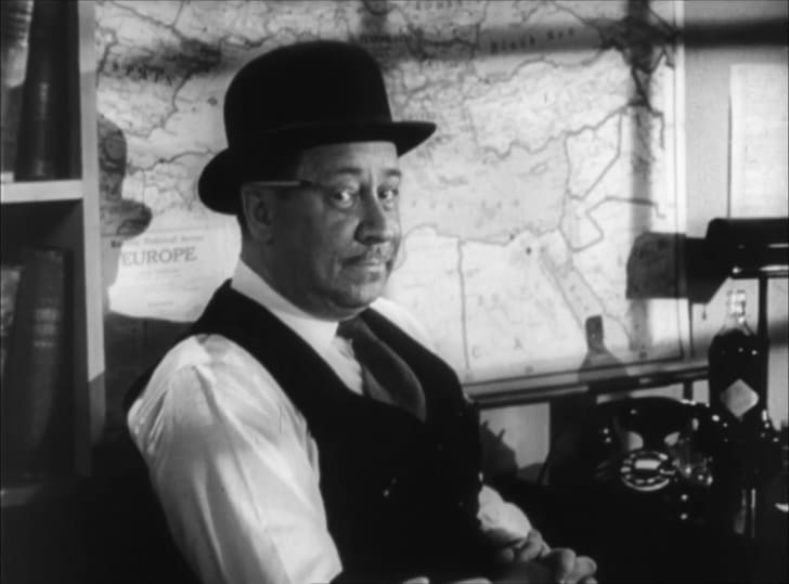 Robert Benchley sits at a desk in a scene from 'Foreign Correspondent.'