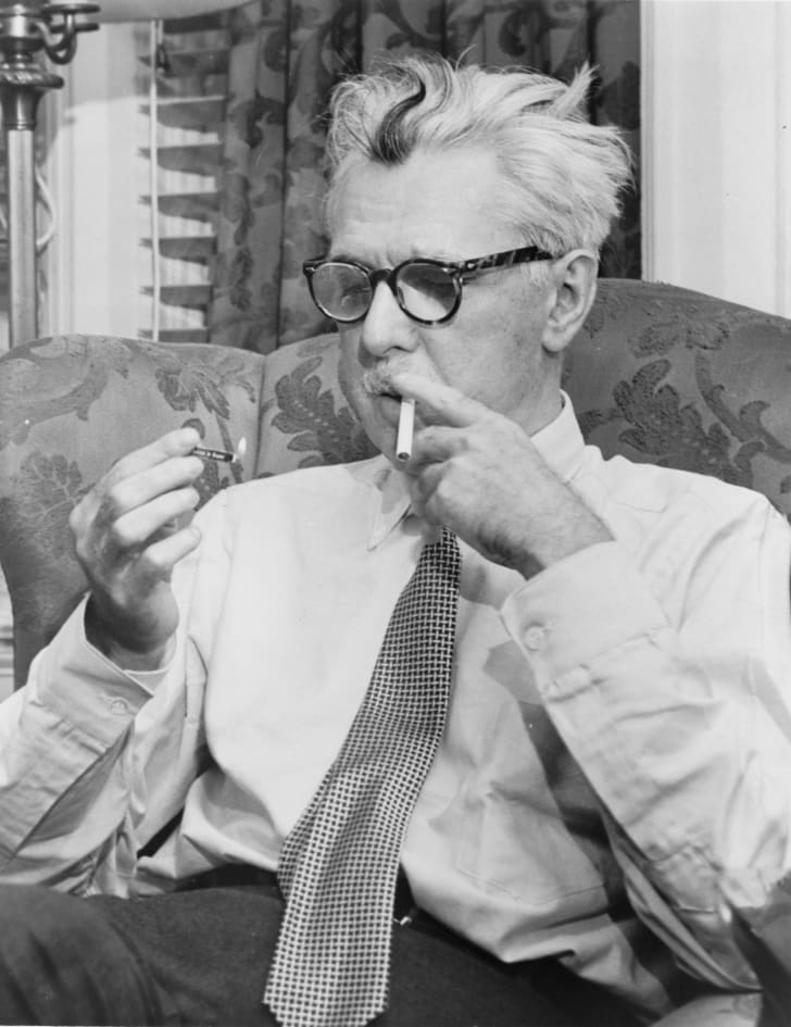 James Thurber smokes a cigarette sitting in an armchair.