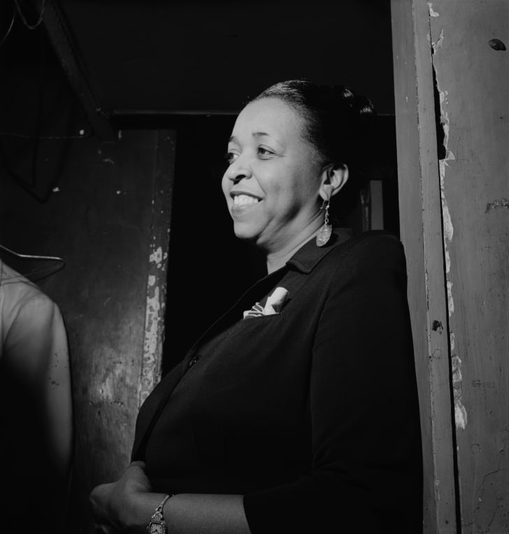 Ethel Waters leans in a doorway.