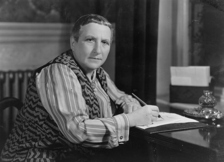 Gertrude Stein sits at a desk with a pen in her hand.