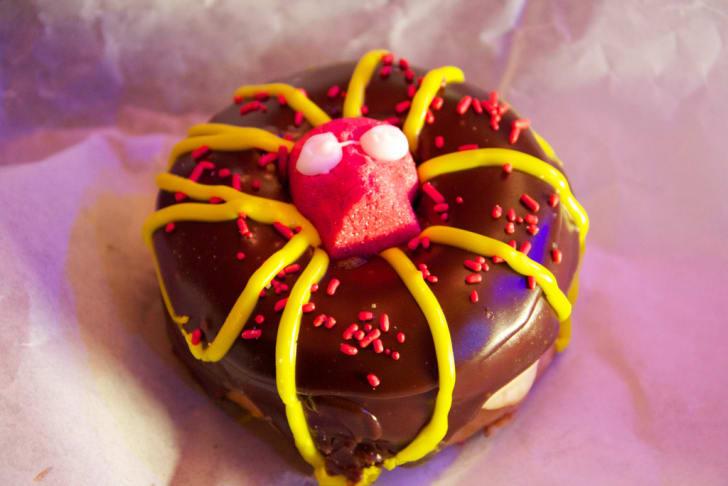 A chocolate doughnut with a candy skull inside the hole.