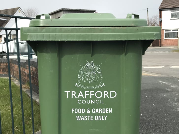 A green trash can with a crest reads 'Trafford Council: Food and Garden Waste Only.'