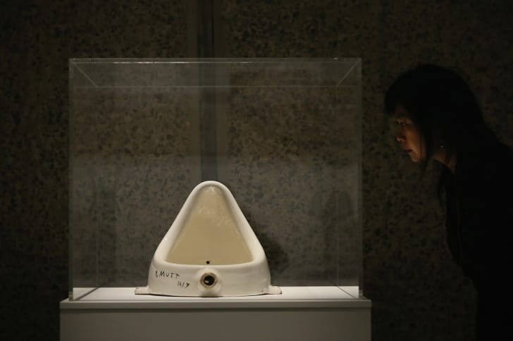 """A woman looking at a replica of Duchamp's """"Fountain"""""""