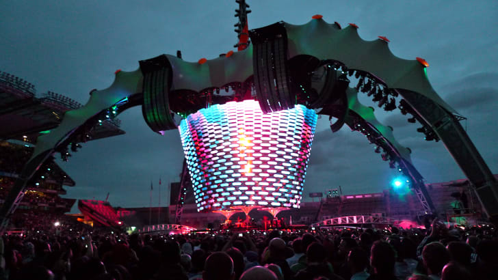 A four-legged, industrial-looking video-and-sound-projection rig rises over a crowd at a concert