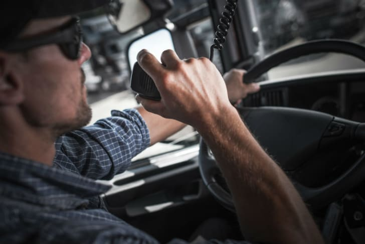 A truck driver uses a CB radio