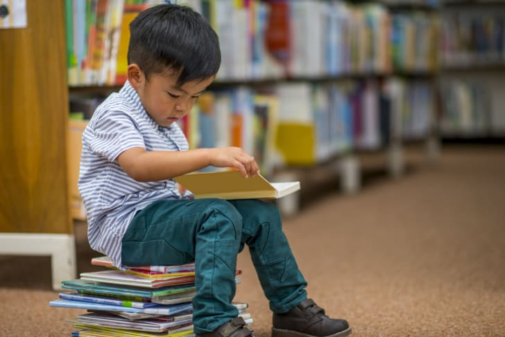 Little boy sitting on a stack of books and reading