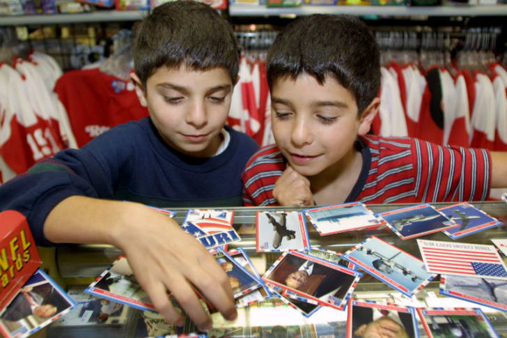 Two kids sort through a Topps 'Enduring Freedom' trading card set