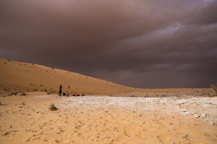 A surveyor stands in the desert.