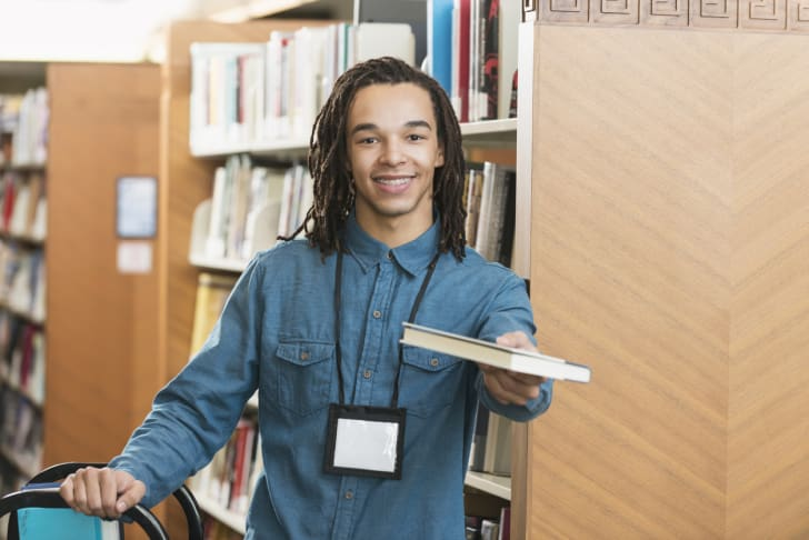 A young man handing over a book at a library