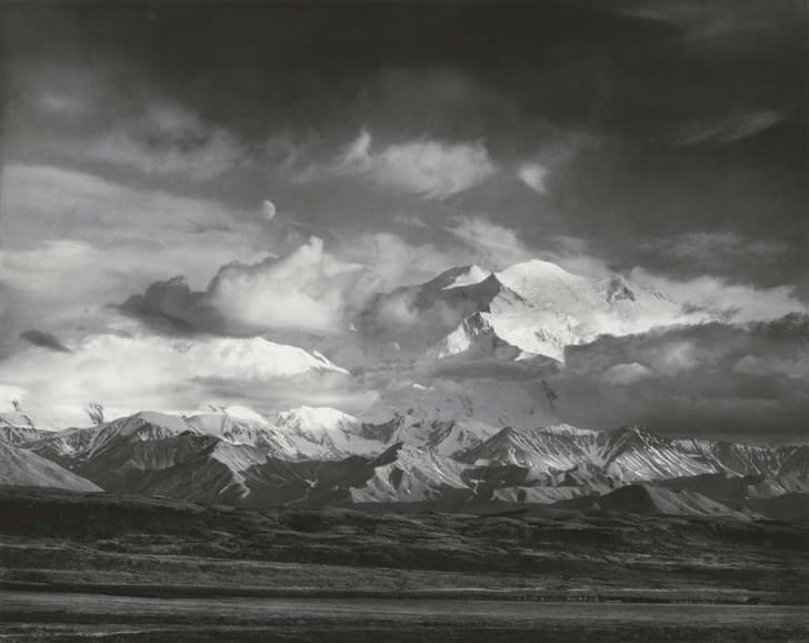 The moon hangs in the sky over Denali in a black-and-white photo