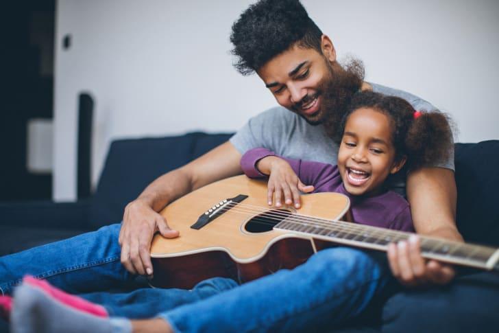 Man and daughter playing guitar