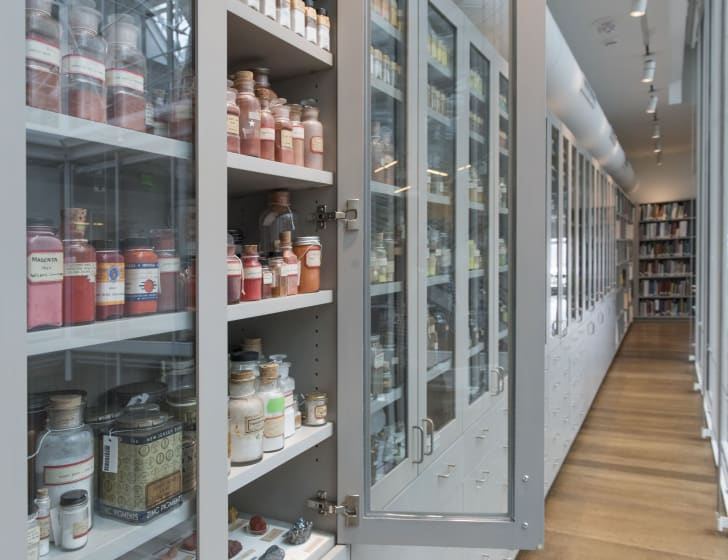 A long hallway with cabinets of colorful jars on the left side