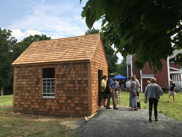 People wander in and out of a replica cabin