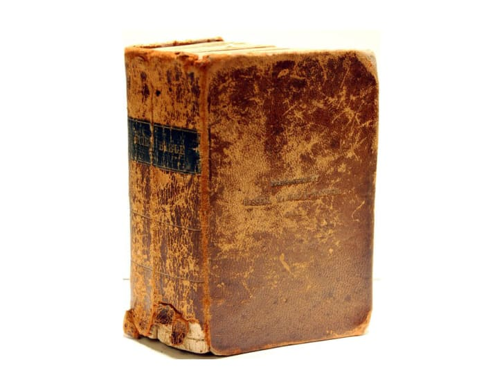 A worn bible against a white background