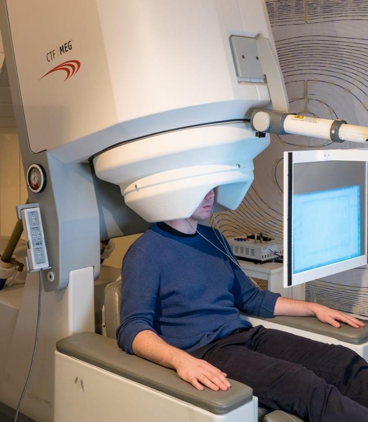 A man sits inside an MEG scanner.