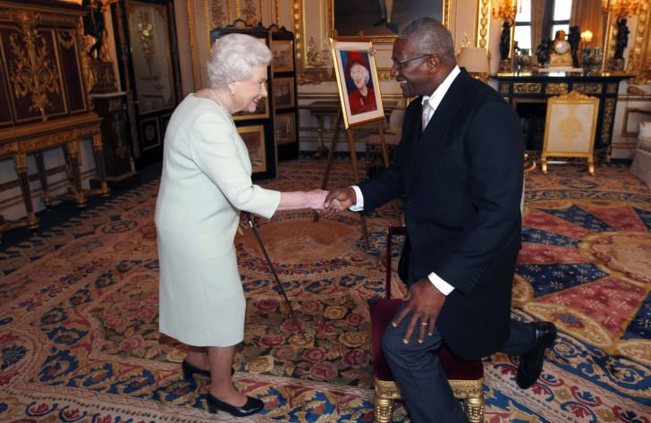Queen Elizabeth II shakes hands after knighting Sir Rodney Williams upon his appointment as Governor-General of Antigua and Barbuda during an audience at Windsor Castle on December 5, 2014 in Windsor, United Kingdom
