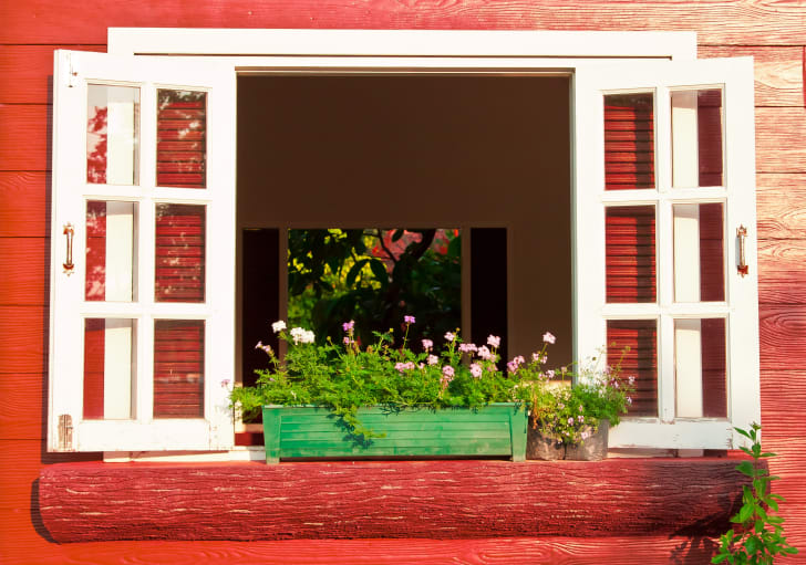 windows open on a red house