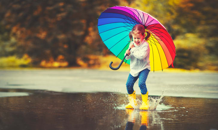 child with rainbow umbrella jumping in puddle