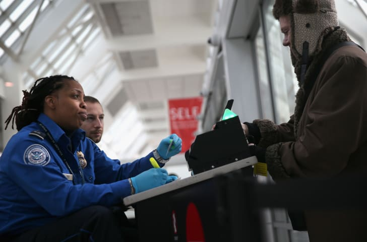 A TSA agent looking at a traveller's documents