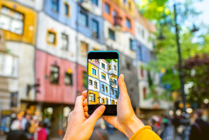 Two hands holding up a phone to photograph a colorful building