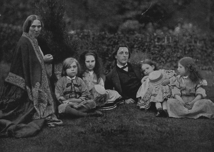 English mathematician, writer and photographer Charles Lutwidge Dodgson, better known as Lewis Carroll (1832 - 1898) with Mrs George Macdonald and four children relaxing in a garden.