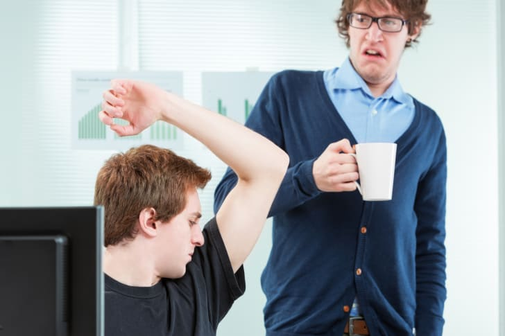 Man smelling his armpits in front of a coworker
