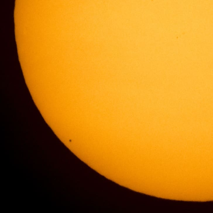 Mercury is seen in silhouette, lower left of image, as it transits across the face of the sun.
