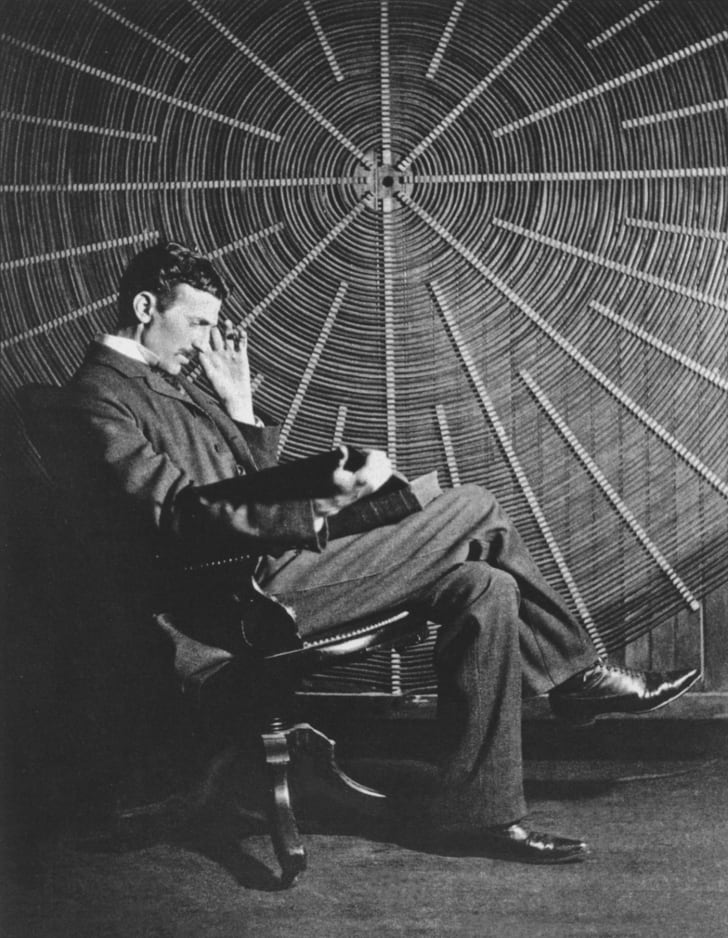 """Nikola Tesla, with Rudjer Boscovich's book """"Theoria Philosophiae Naturalis"""", in front of the spiral coil of his high-voltage Tesla coil transformer at his East Houston St., New York, laboratory."""