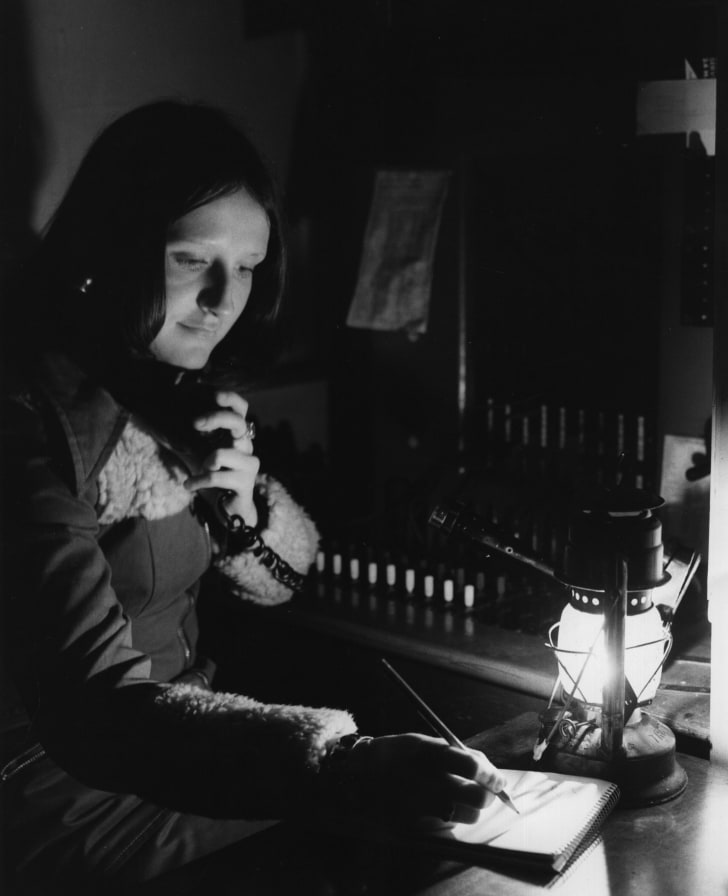 A telephone operator works by hurricane lamp because of energy crisis restrictions in 1974.
