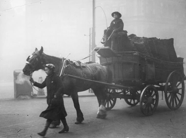 Women coal heavers driving a horse-driven cart loaded with sacks of coal during the First World War.