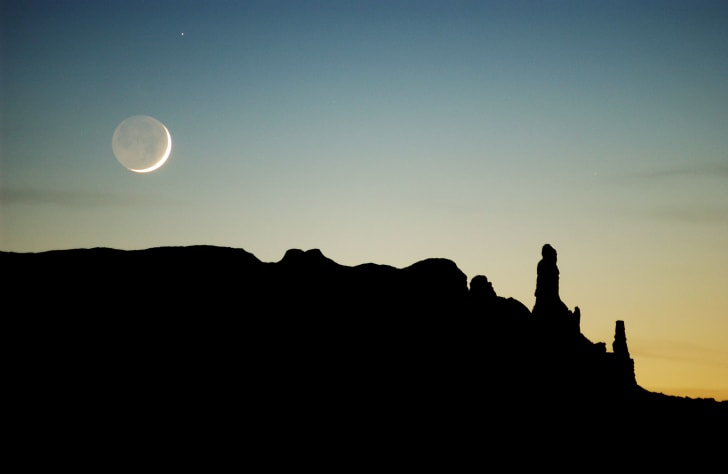 The moon sets over sandstone formations near Round Rock on the Navajo Indian Reservation, Arizona.