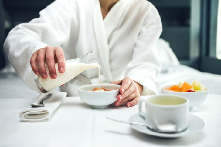 A hotel guest pours milk into a bowl of cereal