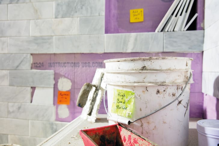 A Post-it Extreme sticks to a dirty bucket on a construction site.