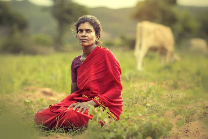 A woman sits in a field