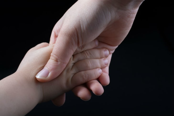 A mother holds her child's hand