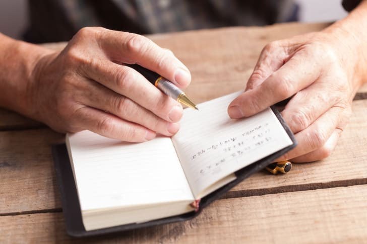 Old man writing in book
