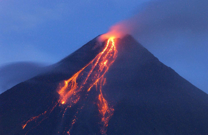 The cloud-covered Mayon volcano spews ash as it erupts near the Philippines