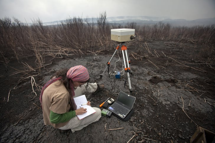 A volcanologist takes gas emission measurements during an assessment mission inside the crater at Mount Nyamulagira