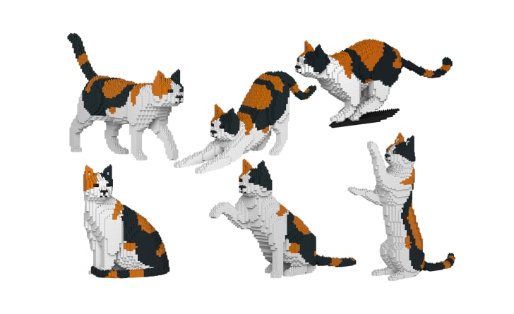 Six different calico cat sculptures in different positions